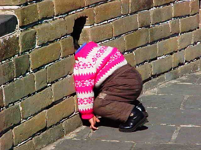 Child with head poked in an opening of the Great Wall of China at Badaling.
