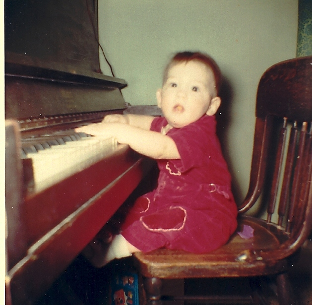 Child playing piano - old upright piano