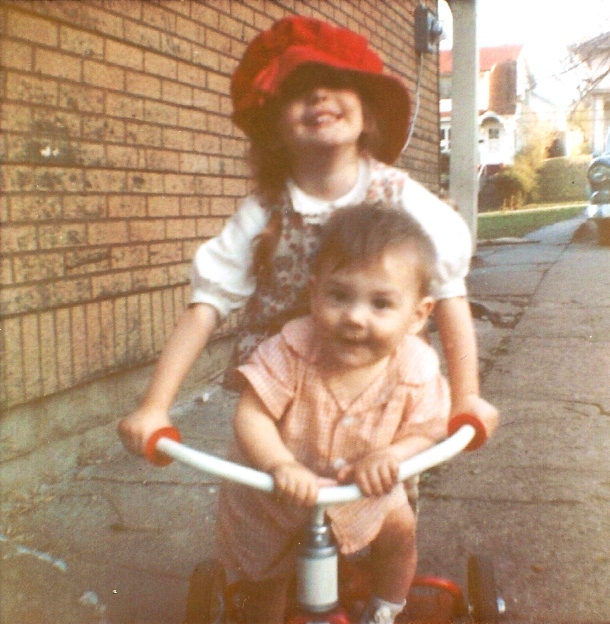 Siblings on trike, tricycle, big sister, floppy red hat