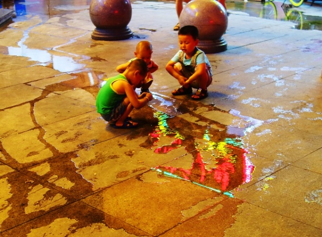 Playing in the water, Chinese boys, colorful reflections, Shanghai, Pudong